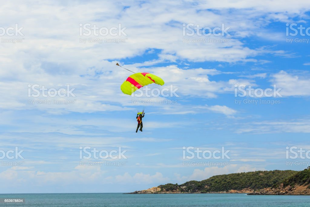 Parachutist coming down the seaside stock photo