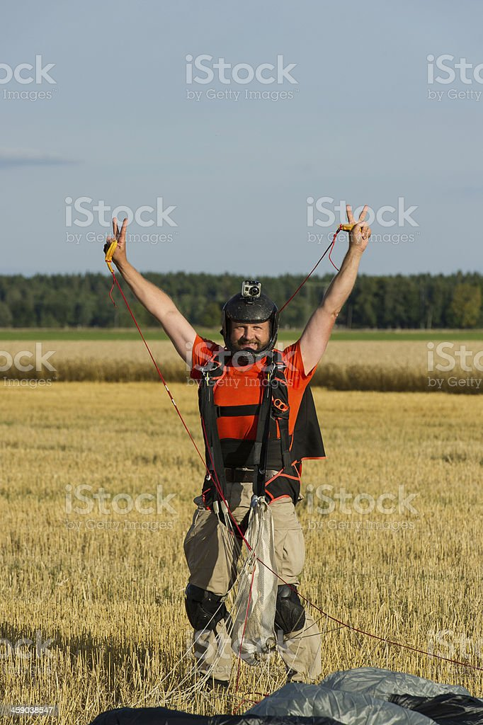 Parachutist doing V-sign after landing royalty-free stock photo