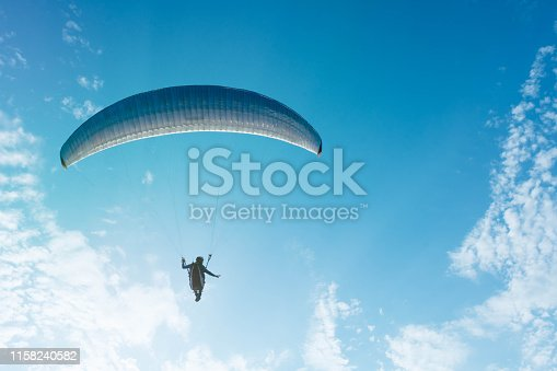 Parashutist soaring in a beautiful blue sky with light clouds. Beautiful planning.