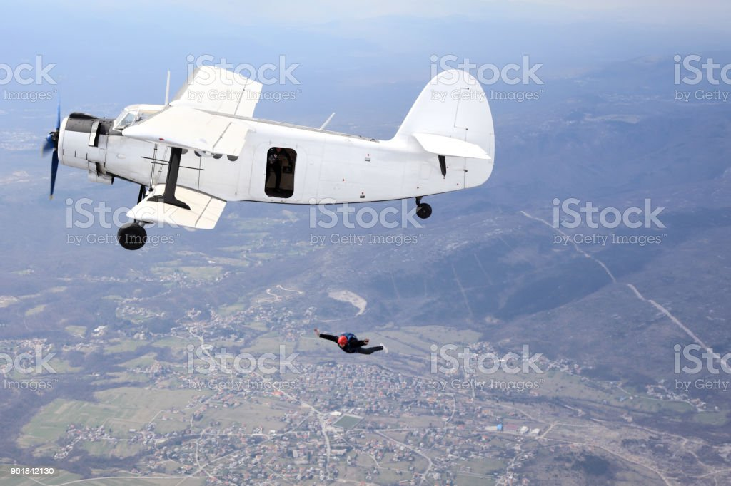 Parachutists jump from a vintage biplane royalty-free stock photo