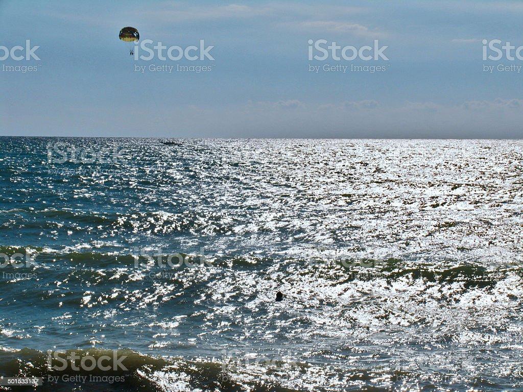 Parachutists over the sea stock photo