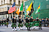 New York, NY, USA - March 17, 2016: Marchers with flags dressed in kilts march in the St Patrick's Day Parade on on 5th Ave in New York City.