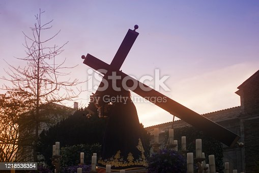Buen Jesus brotherhood, Holy Week parade  Lugo city, Galicia, Spain.  Parade float , Jesus Christ carrying the cross silhouetted, crucifixion scene, cross shape. Sunset background.