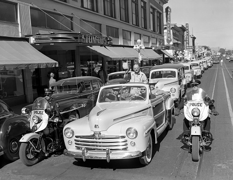 """Tucson, Arizona, USA - November 4, 1947: 1947 Ford Super DeLuxe Sportsman """"woodie"""" convertible leads a parade of new Ford cars in front of Steinfled's department store along Stone Avenue in Tucson, Arizona. The event celebrates the opening of a new Monte Mansfield (in lead car) Ford showroom. Two motorcycle police on Harleys, escort the parade."""