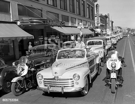 "Tucson, Arizona, USA - November 4, 1947: 1947 Ford Super DeLuxe Sportsman ""woodie"" convertible leads a parade of new Ford cars in front of Steinfled's department store along Stone Avenue in Tucson, Arizona. The event celebrates the opening of a new Monte Mansfield (in lead car) Ford showroom. Two motorcycle police on Harleys, escort the parade."
