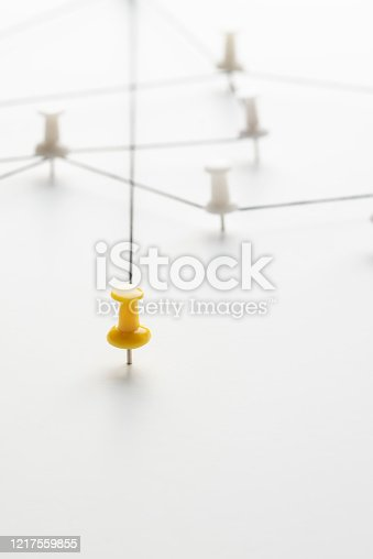 Yellow pin among white pins connected with black string.