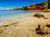 Lonely Adriatic beach with red cliffs and turquoise sea, Vir island location, Dalmatia, Croatia.