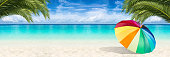 wide paradise beach panorama background with colorful parasol and coco palms