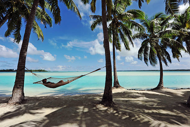 Paradise Hammock A man sleeps in a hammock (in semi silhouette) shaded by palm trees beside a turquoise lagoonSouth Pacific south pacific ocean stock pictures, royalty-free photos & images