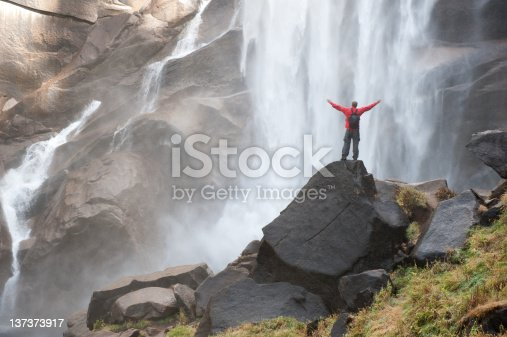 A man with outstretched arms stands in awe of a huge waterfall.
