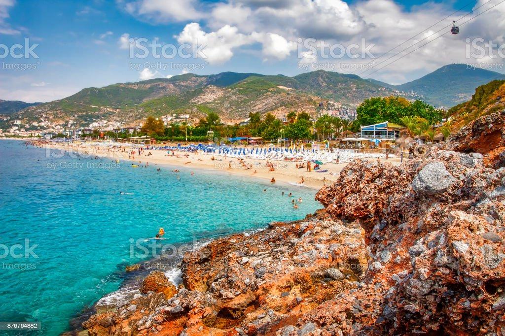 Cennet tropikal resort beach Alanya, Türkiye'de. Deniz ve rocky Dağları bulutlar ile güneşli gün yaz Türk plajda. Yaz tatil dinlenmek. stok fotoğrafı