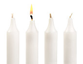 Three paraffin candles and one individual burning candle isolated on white background.