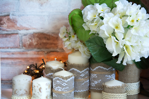 Paraffin candles with a bouquet of white artificial flowers on a brick wall background.