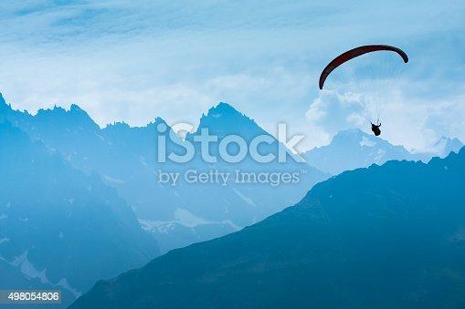 Paraglide shadow figure over Alps peaks