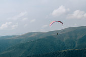 Paraglide silhouette flying over Carpathian peaks and clouds. Extreme sport