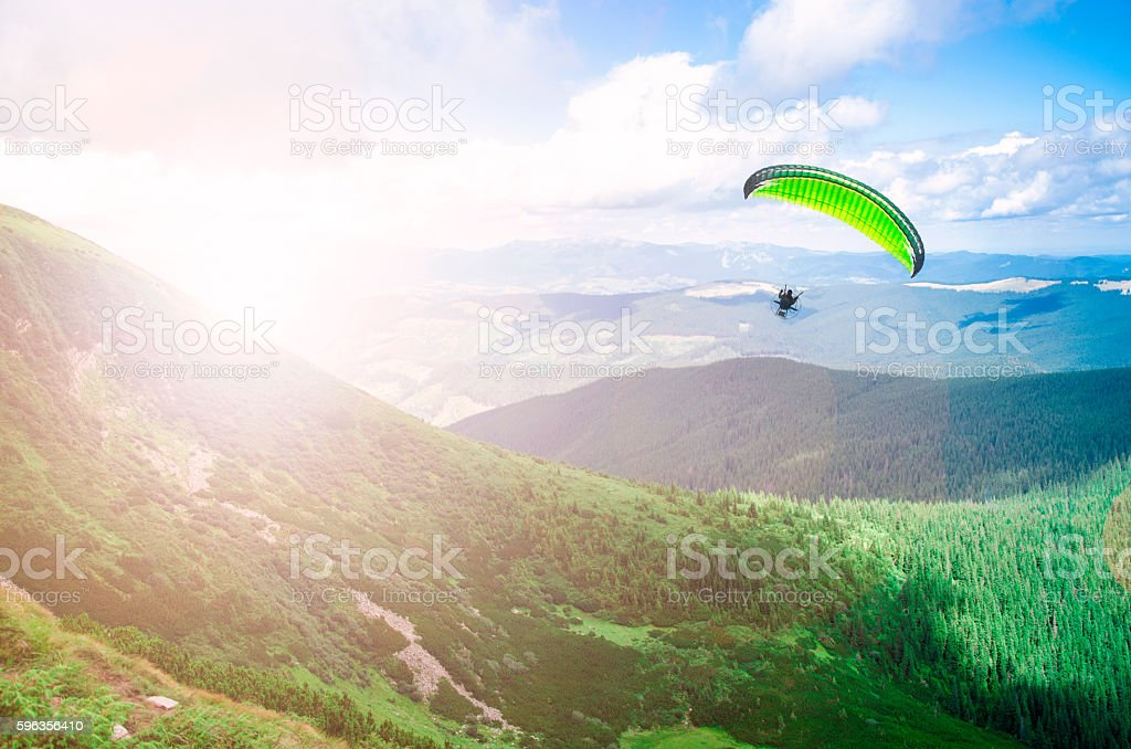 Paraglide silhouette over mountain peaks. royalty-free stock photo