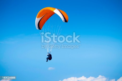 A wide angle view of a paraglider flying high in the sky against a blue background. Space for copy and text. ProPhoto RGB profile for maximum color fidelity and gamut.
