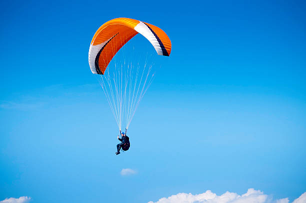 Paraglider, airborne against big blue sky, UK A wide angle view of a paraglider flying high in the sky against a blue background. Space for copy and text. ProPhoto RGB profile for maximum color fidelity and gamut. paragliding stock pictures, royalty-free photos & images