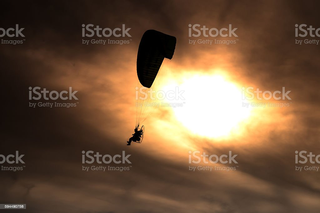Paraglider flies on background of sunset sky stock photo
