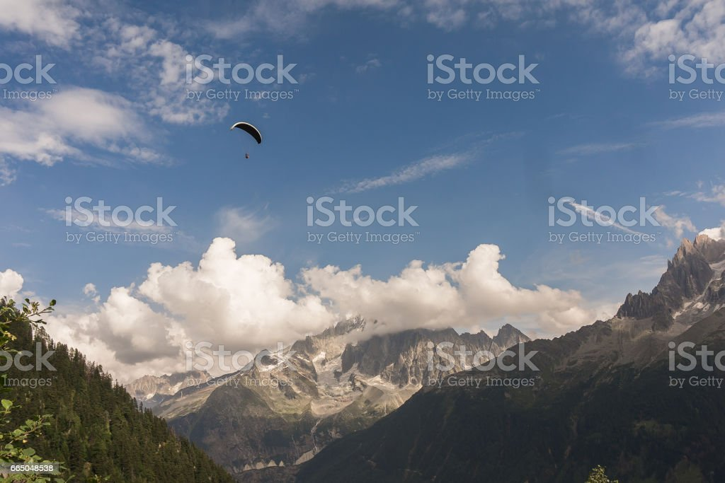 Paraglider flies over the tops of the mountains in summer sunny day stock photo