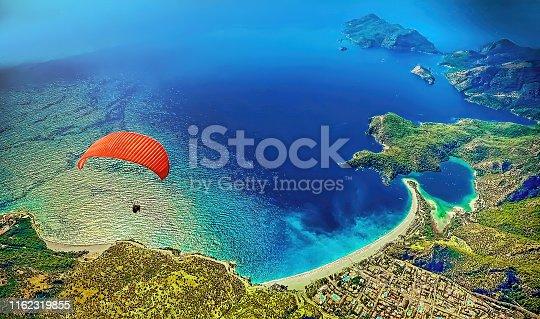Paraglider flying at Fethiye over Blue lagoon in Oludeniz, Turkey