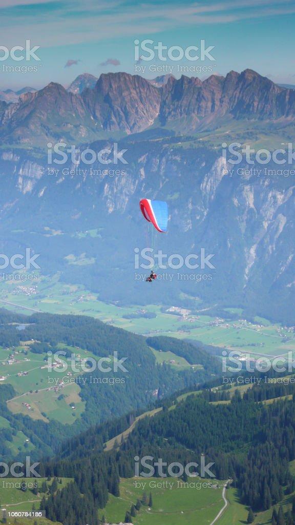 Gleitschirm fliegen in den Himmel über den Bergen der Schweiz – Foto