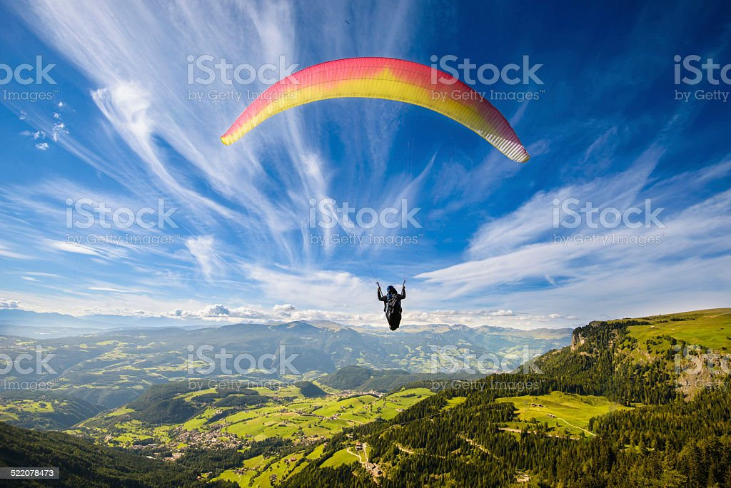 Paraglider flying over mountains stock photo