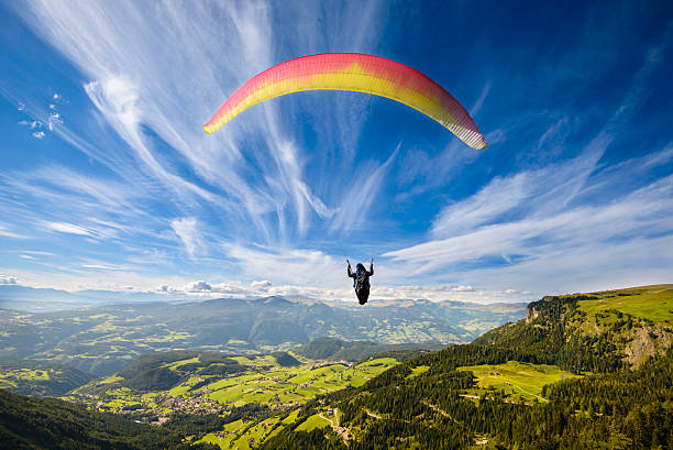 Paraglider flying over mountains Paraglider flying over mountains in summer day parachuting stock pictures, royalty-free photos & images