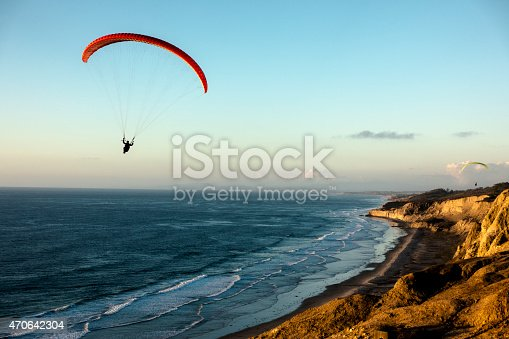 California, La Jolla, Paraglider flying over ocean cliffs at sunset