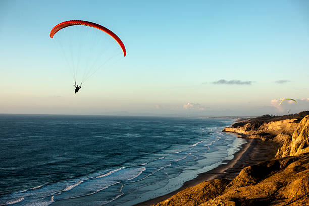 Paraglider flying over ocean cliffs at sunset California, La Jolla, Paraglider flying over ocean cliffs at sunset paragliding stock pictures, royalty-free photos & images