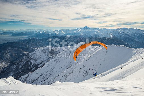 Paraglider flying on snowy slope with bright orange kite. Stunning background of the italian Alps in winter season. Shot taken in backlight, unrecognizable person.Paraglider flying over the mountains with bright orange kite. Stunning background of the italian Alps in winter season. Unrecognizable person.