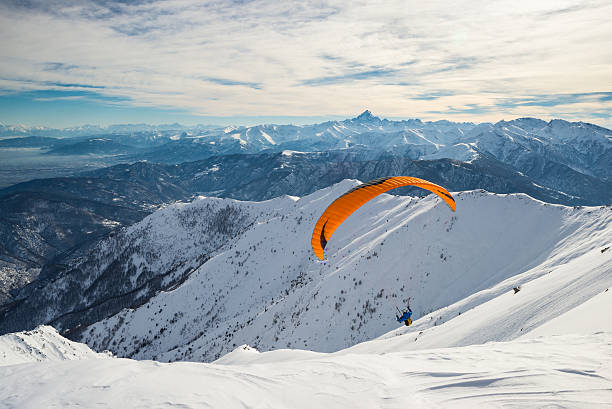 Paraglider flying over the Alps Paraglider flying on snowy slope with bright orange kite. Stunning background of the italian Alps in winter season. Shot taken in backlight, unrecognizable person.Paraglider flying over the mountains with bright orange kite. Stunning background of the italian Alps in winter season. Unrecognizable person. paragliding stock pictures, royalty-free photos & images