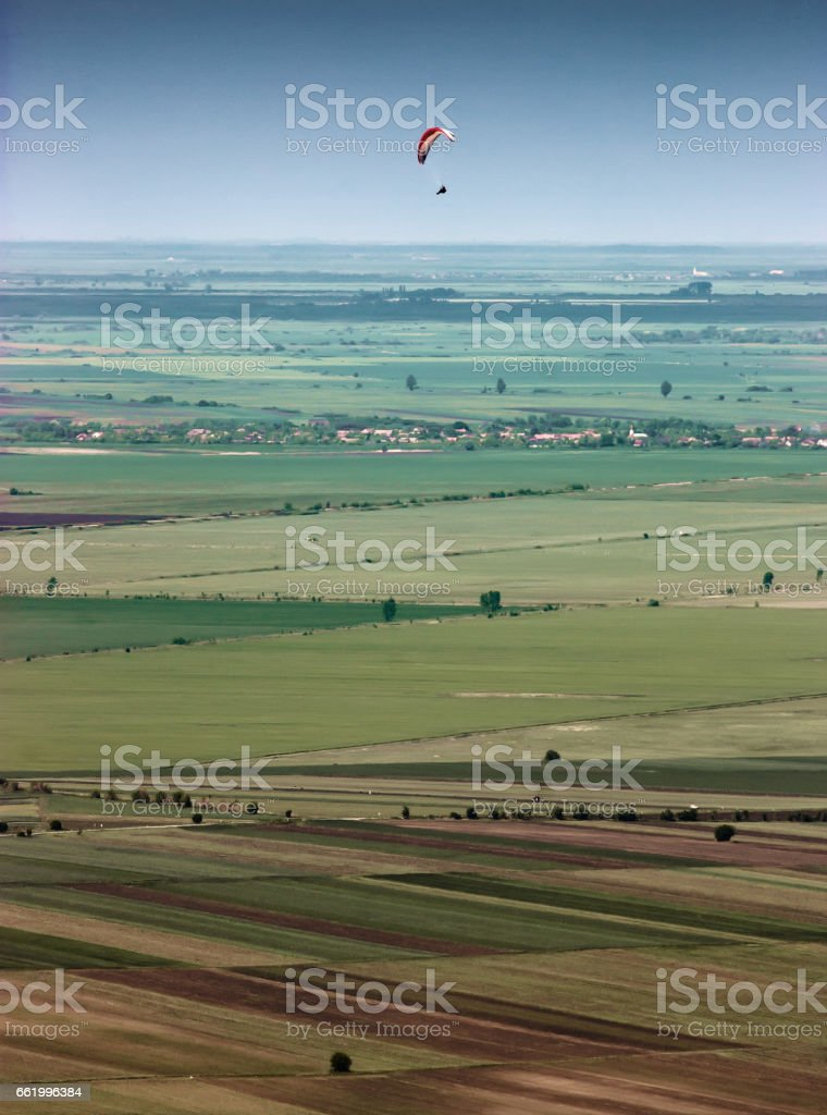 Paraglider flying over the endless fields royalty-free stock photo