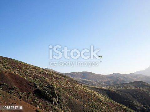 Paraglider flying over the Teide National Park and silhouette of the Astronomical Observatory of Tenerife, Canary Islands under blue sky.