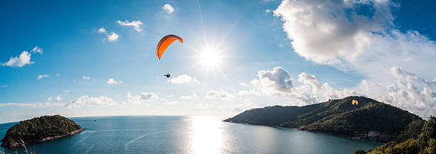 Paraglider flying over the water stock photo