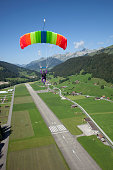 Paraglider glides over plane runway in Alps