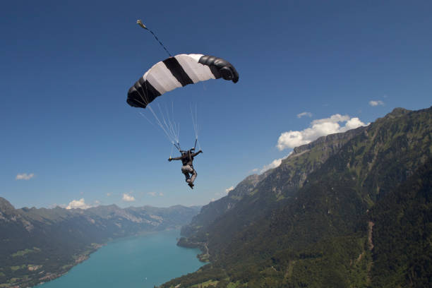 Paraglider glides through mid-air clouds and mountains behind parachuting stock pictures, royalty-free photos & images