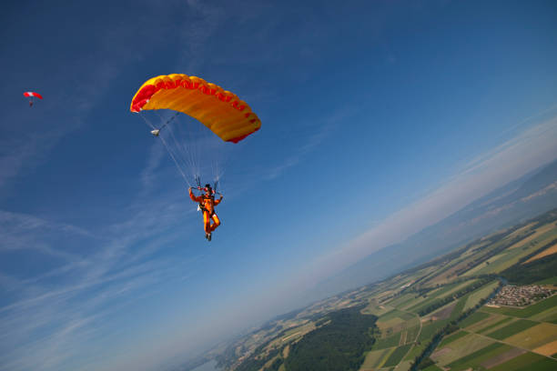 Paraglider glides towards the earth Earth and sky behind parachuting stock pictures, royalty-free photos & images