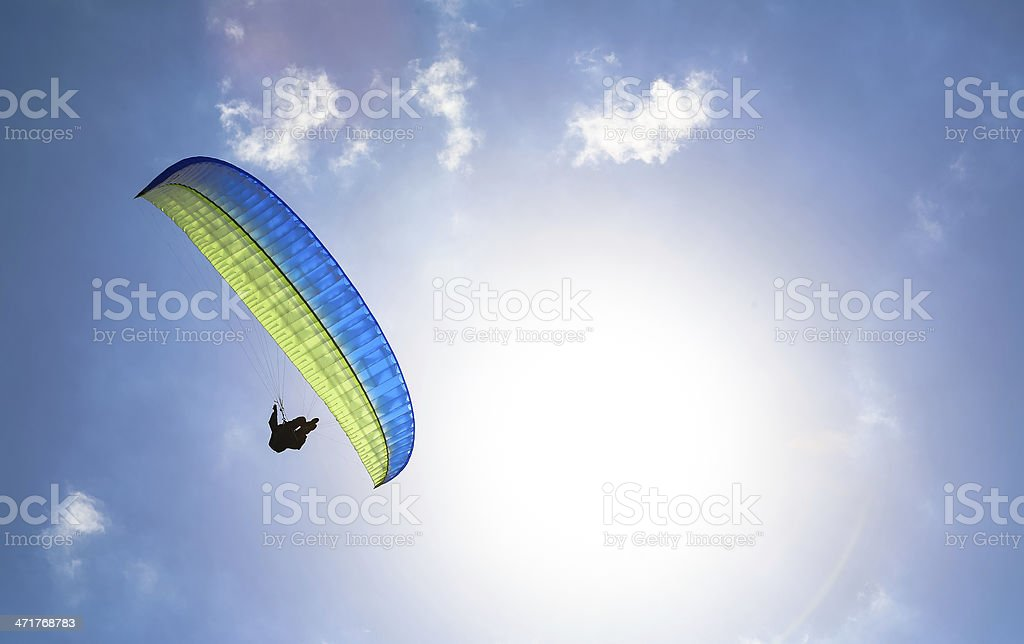 Paraglider hovers in a sunny blue sky royalty-free stock photo