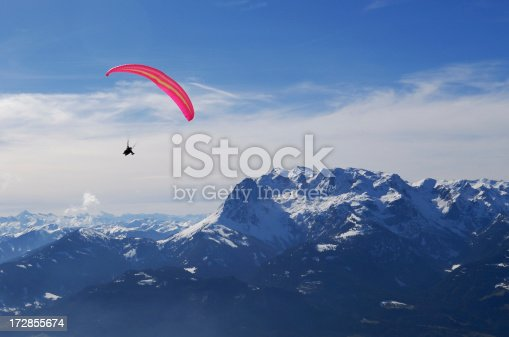 A paraglider soars over the Alps.
