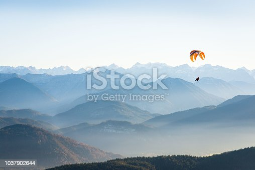 istock paraglider in the mountains 1037902644