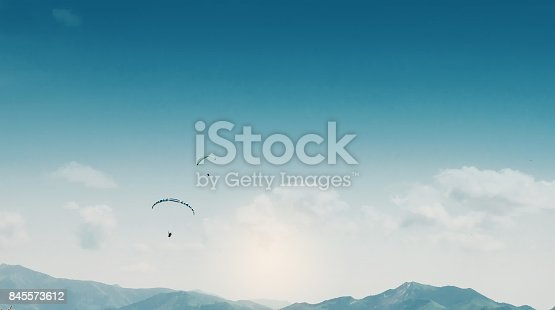 Paraglider is flying above the blue mountains