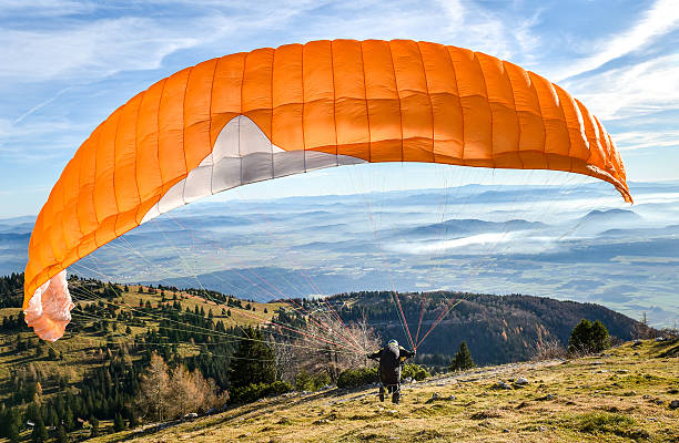 Paraglider is starting  to start his flight. Paraglider is starting  to start his flight. Looking at beautiful valley below with clouds and mist. paragliding stock pictures, royalty-free photos & images