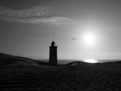 Paraglider near lighthouse at sunset
