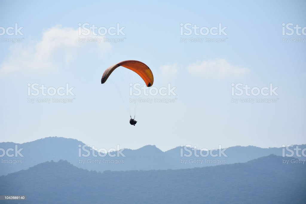 Paraglider on a clear day for background usage. Spaces for type. stock photo