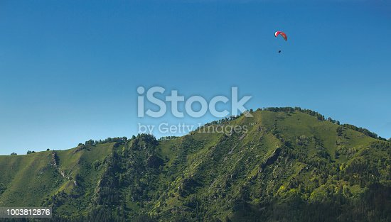 The paraglider flies over the mountain on a sunny day