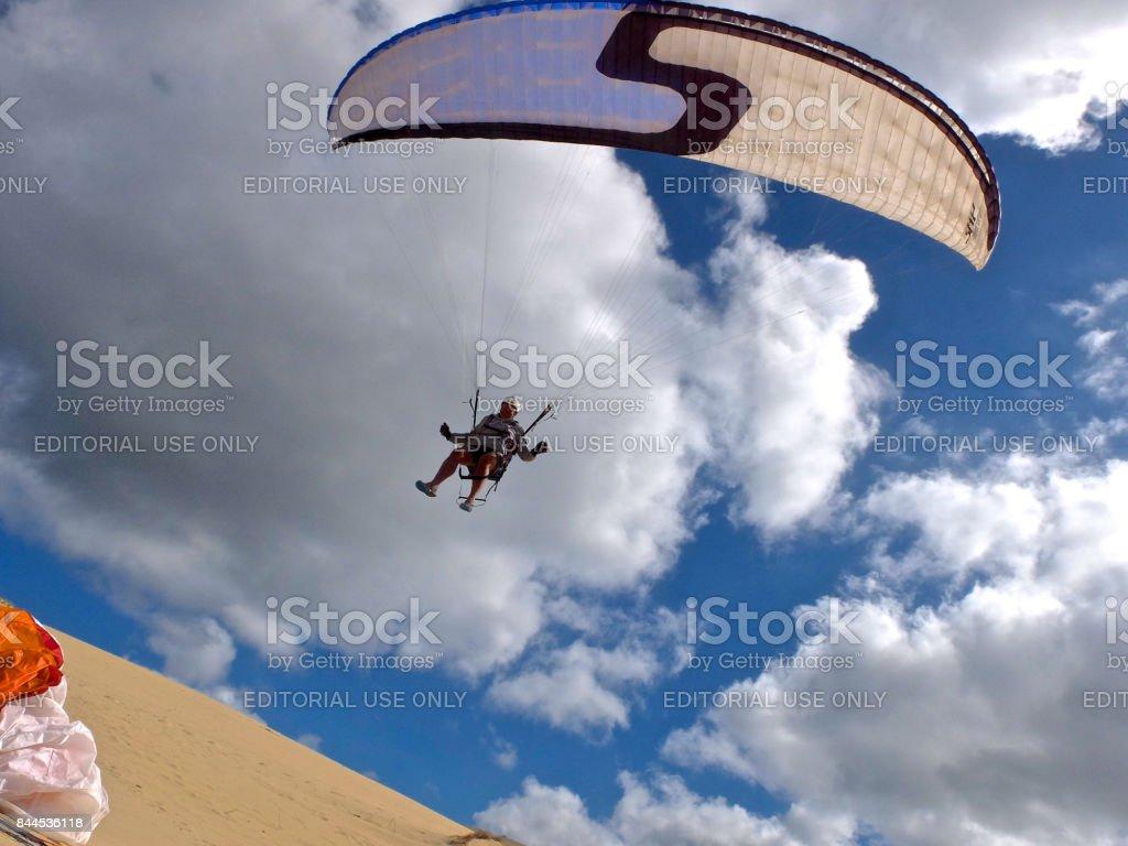 Paraglider pilot landing on sand dune stock photo