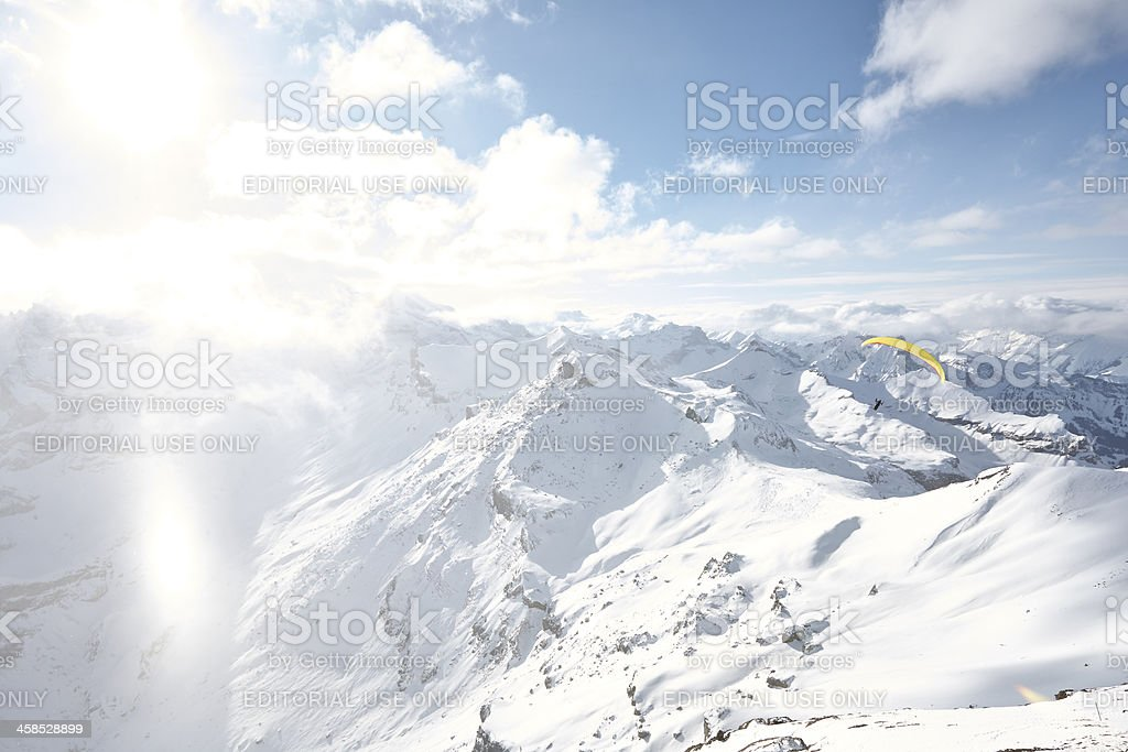Paraglider roams above the snow covered mountains royalty-free stock photo