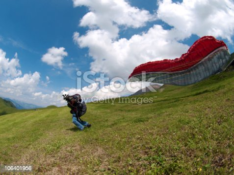 a paraglider short before take of during a sunny summer day.