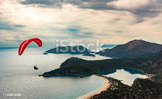 istock Paraglider tandem flying over the Oludeniz Beach and bay at idyllic atmosphere. Oludeniz, Fethiye, Turkey. Lycian way. Amazing Blue Lagoon detail. Summer and holiday concept. 1140623495
